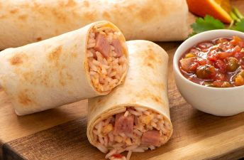 Two ham breakfast burritos with salsa