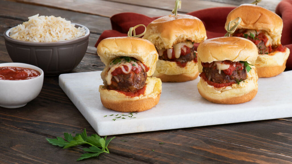 Three meatball sliders with marinara and cheese