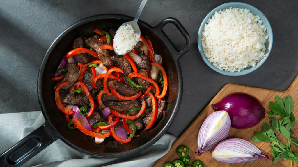 Mexican spiced beef in a pan with peppers and red onion
