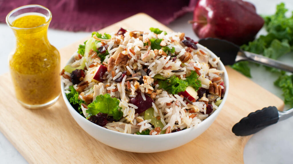 Salad bowl with rice, kale, chicken and a bottle of orange dressing