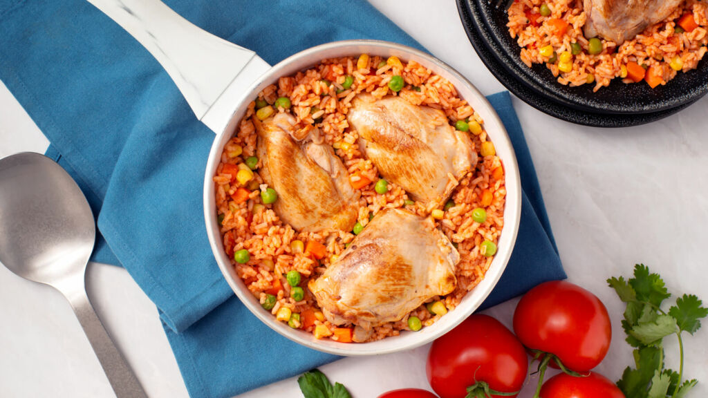 Traditional arroz con pollo with chicken thighs, peas and stewed tomatoes