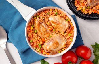 Arroz tradicional con muslos de pollo, guisantes y tomates