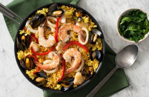 Sartén de paella española con mariscos y arroz amarillo