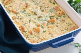 Shallow baking dish with baked chicken, cheese and rice