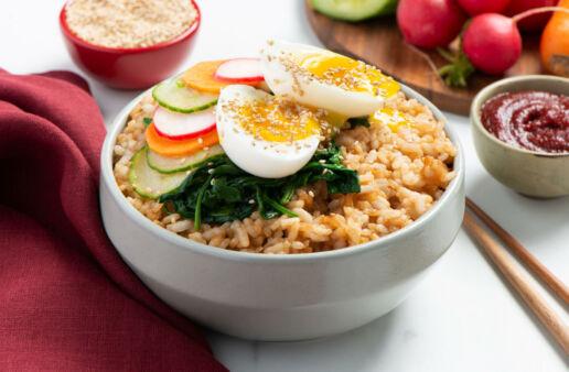 Bowl blanco con arroz de grano corto, vegetales encurtido y huevo escalfado