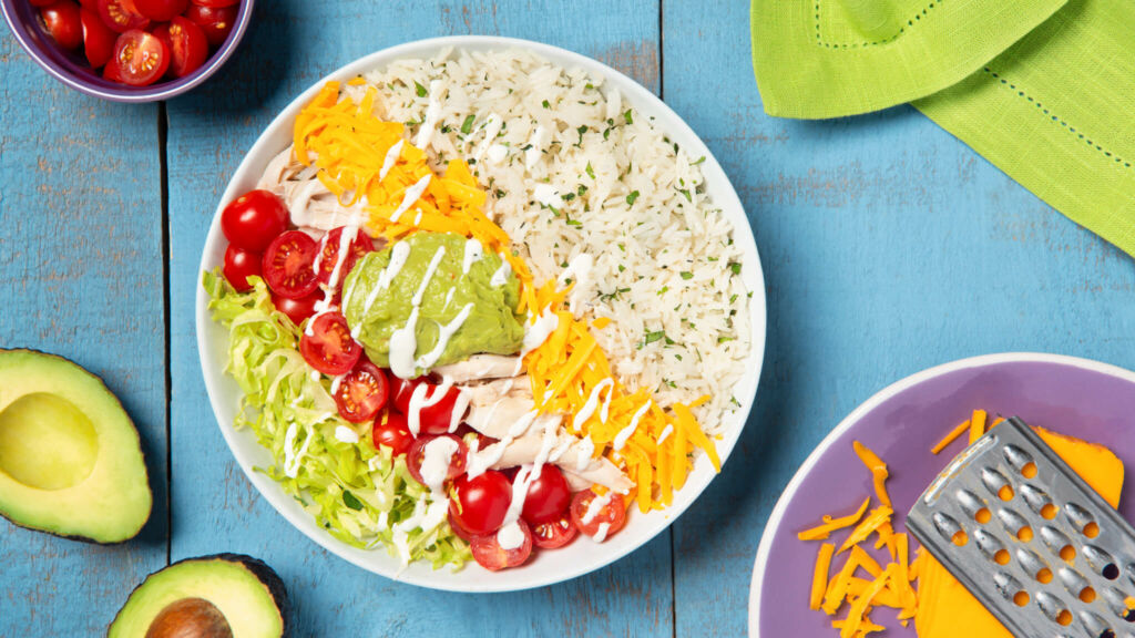 Burrito bowl with cilantro lime rice, cheddar cheese, shredded chicken and guacamole