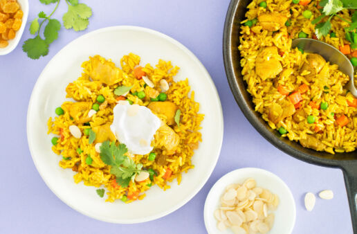 Chicken biryani rice bowl with chopped cilantro and greek yogurt