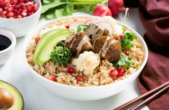 Power bowl with fried rice, falafel, tahini sauce, an avocado and soy sauce