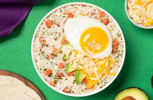 Huevos rancheros rice bowl con tomatoes, aguacate y arroz listo para servir