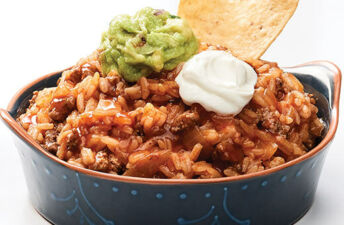 Beefy Enchilada rice dip with guacamole and sour cream