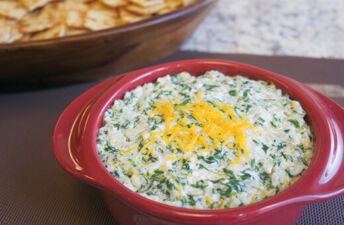 Cheesy spinach and rice dip in a red microwave bowl