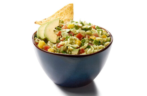 Bowl with guacamole rice dip, mango, tomatoes and nachos