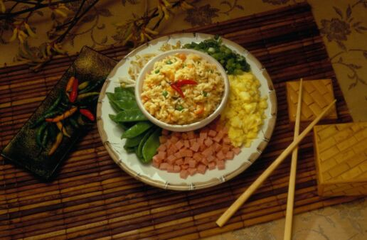 Arroz frito en un bowl con jamón, huevos, vegetales y palillos chinos