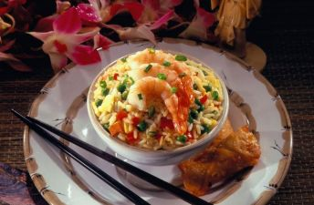 Chopsticks and bowl with fried rice, peas, shrimp and pork
