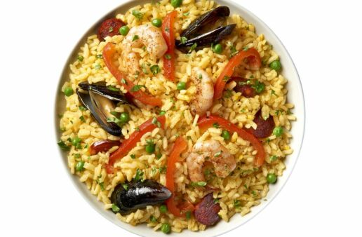 Paella dish with parboiled rice, shrimp, red pepper and chorizo