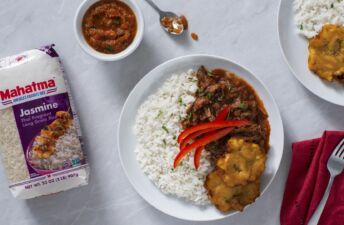 Shredded flank steak and vegetables with tomato-based sauce, fried plantains and Jasmine Rice