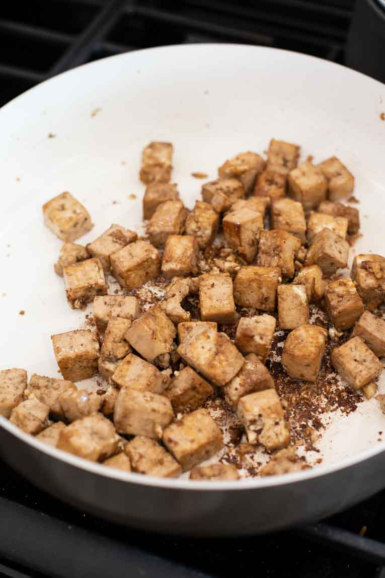 cooking tofu in the pan with sesame oil