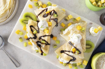 rice-crepes-with-kiwi-pineapples-mango-coconut-whipped-cream-and-chocolate-syrup