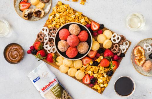 colorful-dessert-board-with-sweet-arancini-fresh-fruit-caramel-pop-corn-and-pretzels